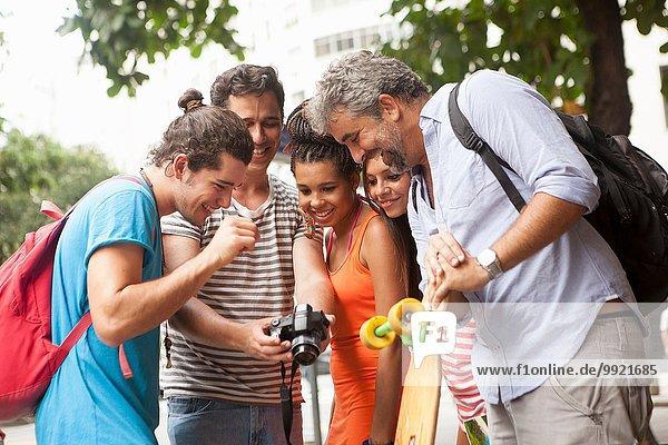 Fünf erwachsene Freunde beim Betrachten von Fotos auf Digitalkamera  Stadt Copacabana  Rio De Janeiro  Brasilien