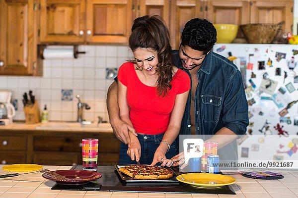 Junges Paar beim Pizzaschneiden in der Küche