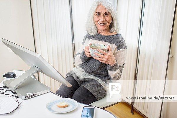 Porträt einer älteren Frau  die am Computer sitzt.