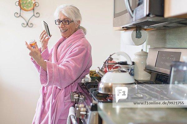 Seniorin steht in der Küche und hält eine Flasche mit verschreibungspflichtigen Medikamenten  während sie auf dem Smartphone spricht.