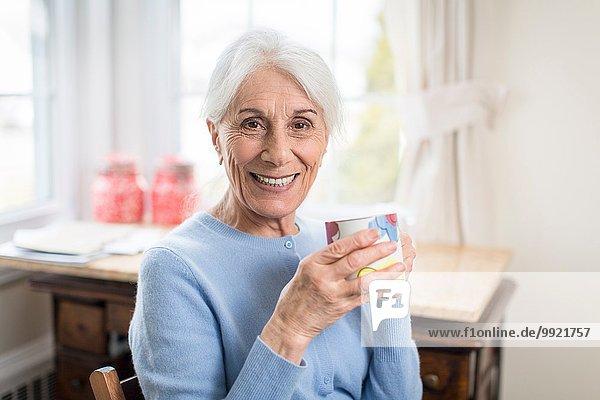 Porträt der lächelnden Seniorin zu Hause mit Pokal
