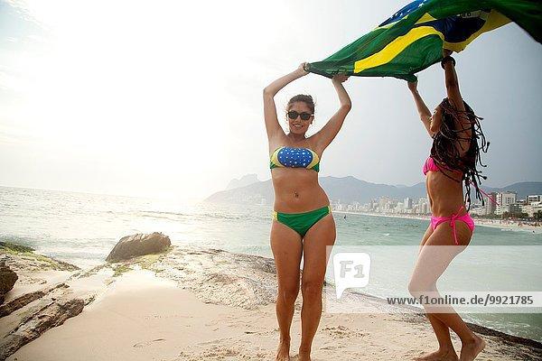 Portrait of two young women dancing whilst holding up Brazilian flag  Ipanema beach  Rio De Janeiro  Brazil