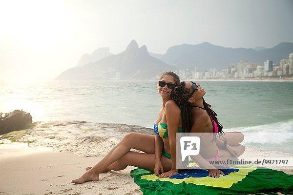Porträt zweier junger Frauen auf brasilianischer Flagge  Strand von Ipanema  Rio De Janeiro  Brasilien
