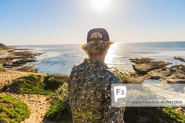 Junger Mann stehend  Blick aufs Meer  Rückansicht