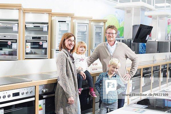 Porträt der Familie mit zwei Kindern beim Durchstöbern von Kochfeldern im Elektronikgeschäft