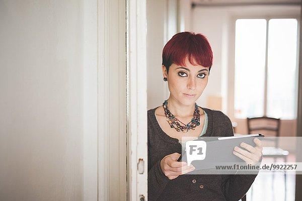 Junge Frau zu Hause mit digitalem Tablett