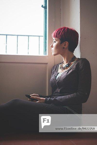 Junge Frau am Fenster sitzend  Smartphone haltend
