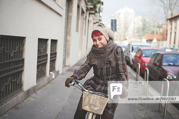 Portrait of young woman riding bicycle  wearing winter clothes