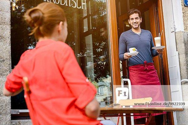 Junge Frau  die vor dem Café sitzt  Caféarbeiterin  die Getränke bringt.