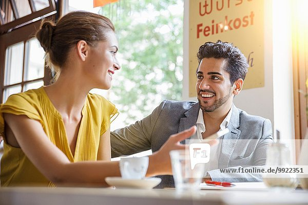 Junges Paar im Cafe sitzend  sprechend  Blickwinkel niedrig