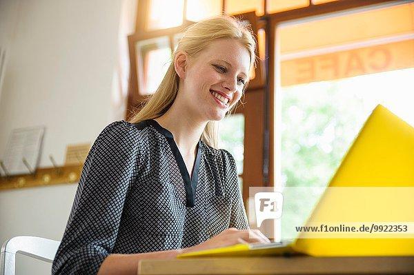 Junge Frau im Café sitzend  mit Laptop  Blickwinkel niedrig