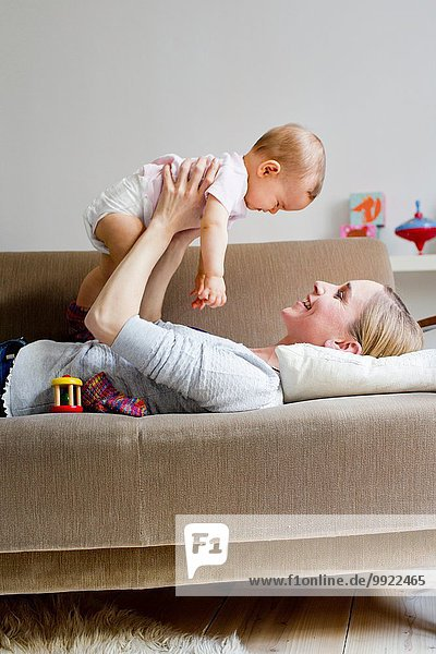 Mother lying on sofa  holding baby girl in air