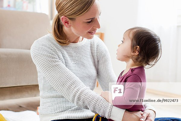 Mutter und Kind sitzen von Angesicht zu Angesicht.