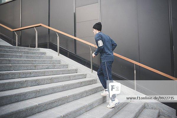 Junger männlicher Läufer  der die Stadttreppe hinaufgeht.