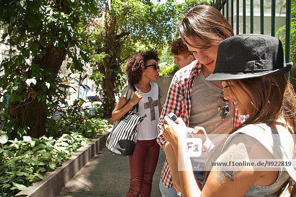 Studentin mit Freunden auf dem Handy