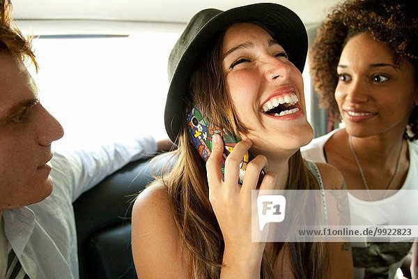 Three friends in car  woman on cell phone