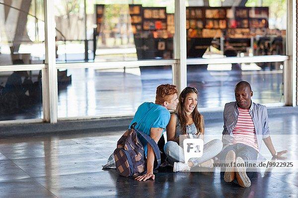 Hochschulstudenten auf dem Boden sitzend