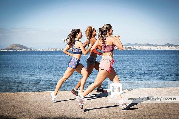 Drei junge Frauen beim Joggen am Strand