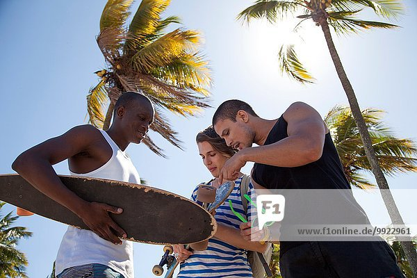 Young man holding skateboard with friends  low angle