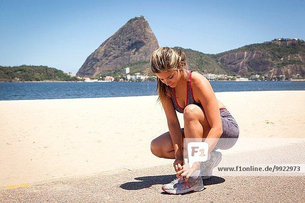Junge Frau beim Schnürsenkelbinden am Strand  Rio de Janeiro  Brasilien