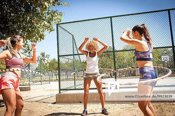 Drei junge Frauen mit Hula-Reifen um die Taille  im Freien