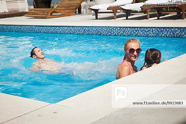 Young family in swimming pool together