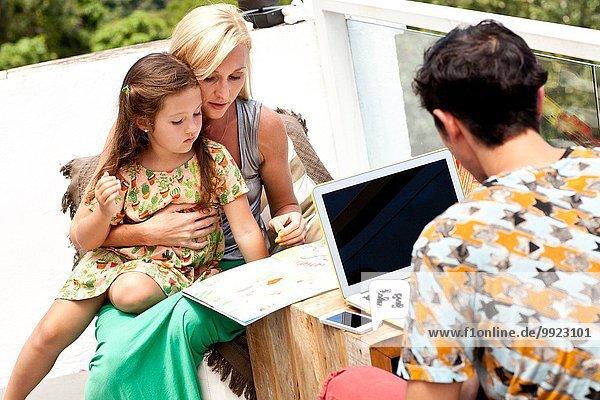 Familie sitzt am Tisch auf dem Balkon  Mutter und Tochter schauen durch das Buch  während Vater den Laptop benutzt.