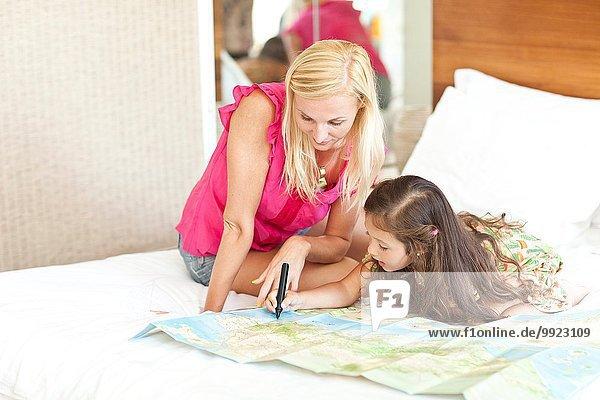 Mutter und Tochter auf dem Bett liegend  mit Blick auf die Karte