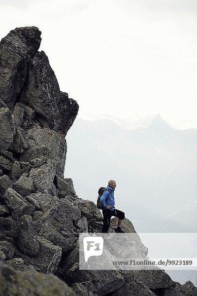 Erwachsener Mann auf Felsen stehend  Wallis  Schweiz