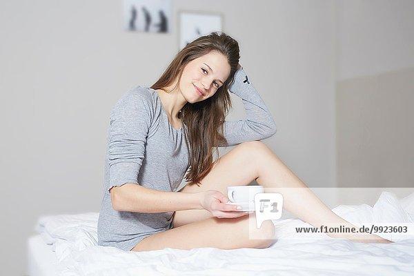 Porträt einer jungen Frau  die auf dem Bett sitzt und Kaffee trinkt.