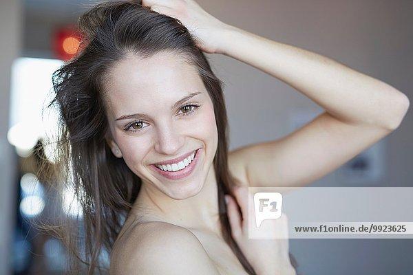 Porträt der schönen jungen Frau mit der Hand im Haar