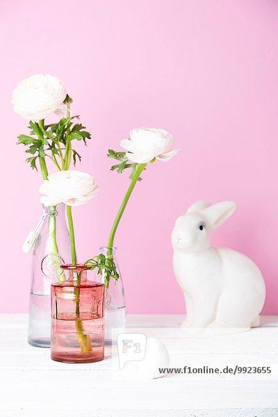 Stilleben von Schnittblumen in Flaschen  weißer Osterhase und Vogel