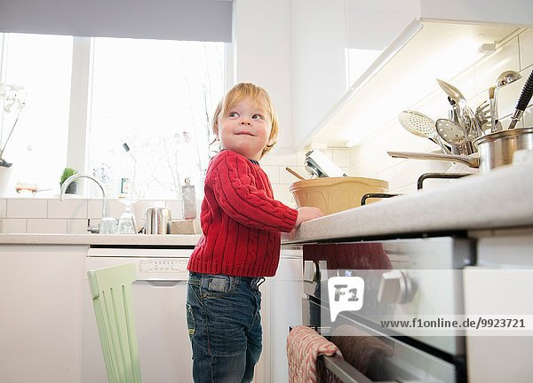 Boy standing on chair in kitchen