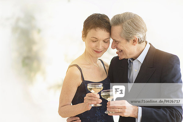 Elegant senior couple celebrating their anniversary with champagne toast