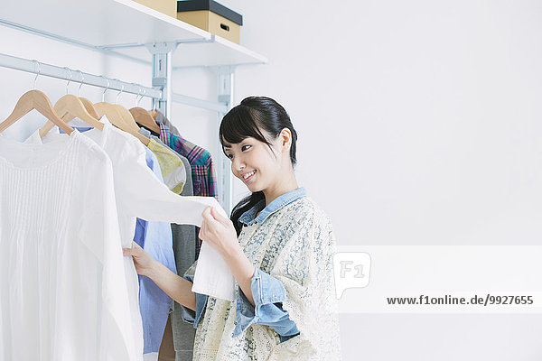 Young woman with long hair choosing clothes in a walk in closet
