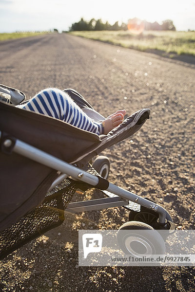 Low-section of baby girl (6-11 months) in stroller