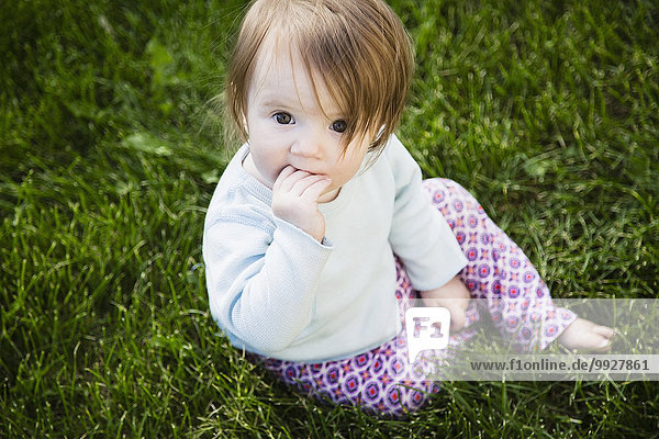 Portrait of baby girl (6-11 months) with hand in mouth