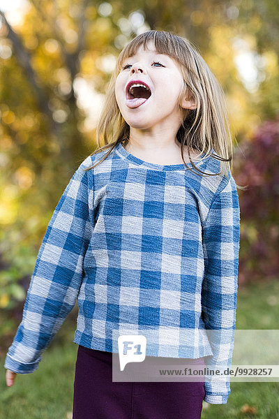Young girl (4-5) with sticking out tongue