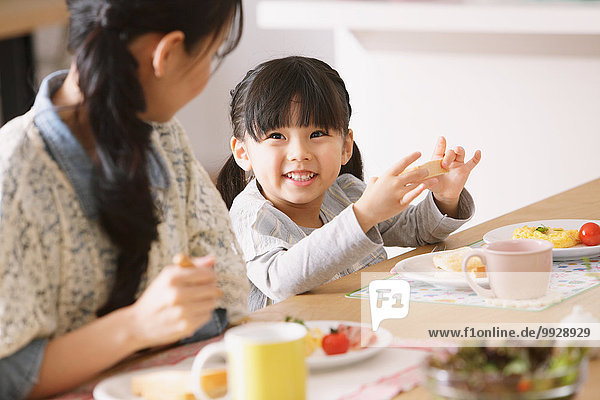Young adult mother and daughter smiling at each other while having breakfast