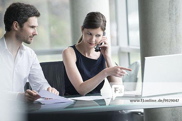 Geschäftsfrau  die die Aufmerksamkeit des Kollegen auf den Computerbildschirm lenkt