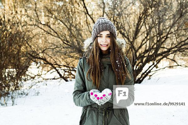 Caucasian girl holding snow in field