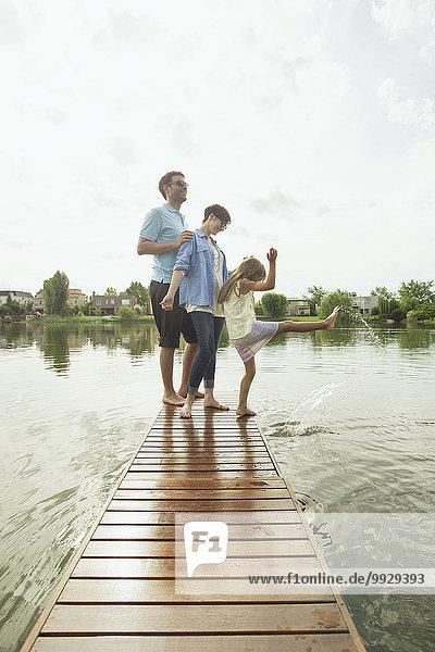 Familie mit kleiner Tochter  die am Ende des Seepiers steht