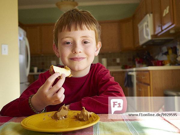 Europäer Junge - Person Mittagspause Pause Apfel essen essend isst Erdnuss Butter