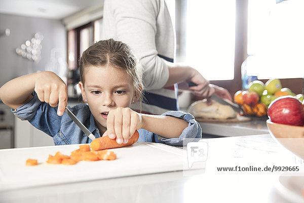 Kleines Mädchen hilft bei der Zubereitung des Essens in der Küche