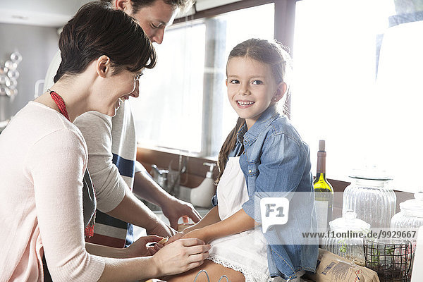 Family spending time together in kitchen  girl sitting on counter holding mother's hands