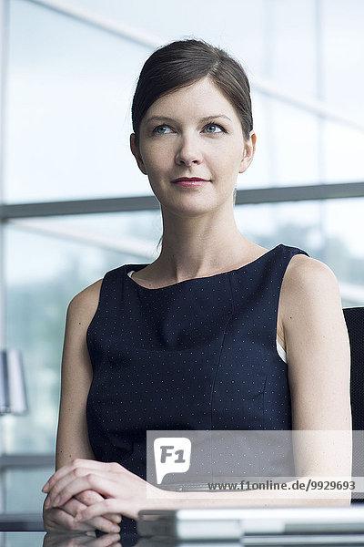 Geschäftsfrau sitzt am Schreibtisch  schaut in Gedanken weg  Porträt