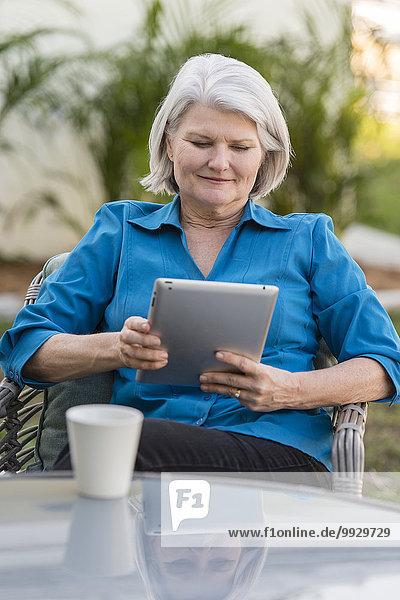 benutzen Europäer Frau Garten Tablet PC alt Hinterhof