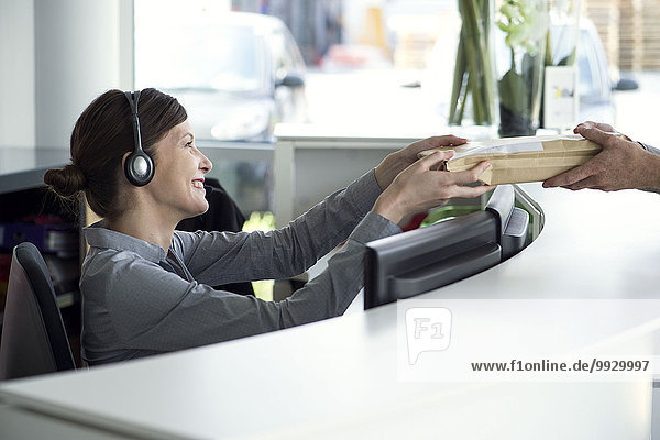 Receptionist accepting package from delivery person