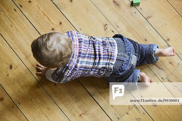Kleiner Junge krabbelt auf dem Boden  Blick nach oben Kleiner Junge krabbelt auf dem Boden, Blick nach oben