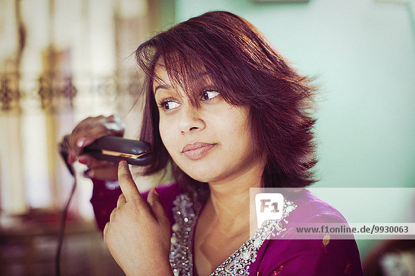 Brunette woman straightening her hair